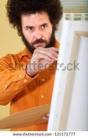 Mature painter in a bright, orange shirt, working in his studio on a painting.