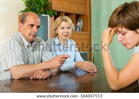 Mature parents  and adult daughter having serious talking in home interior