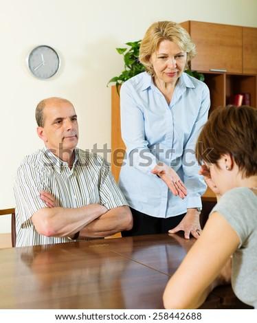 Mature parents berates her  adult daughter  in interior - stock photo