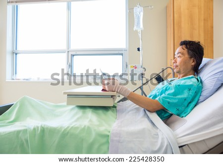 Mature patient using digital tablet while reclining on bed in hospital - stock photo