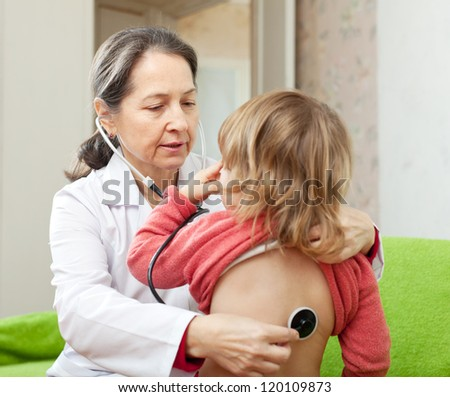 mature pediatrician doctor examining child with  stethoscope. Focus on woman