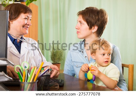 Mature pediatrician doctor talking with mother of baby at clinic office