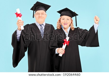 Mature people celebrating their graduation on blue background