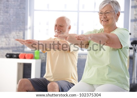 Mature people exercising happily in the gym. - stock photo