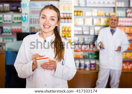 Mature pharmacist and female assistant working at farmacy reception