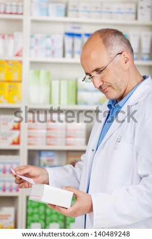 mature pharmacist holding package and prescription in hands - stock photo