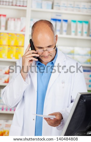 Mature pharmacist holding prescription paper while using cordless phone in pharmacy - stock photo