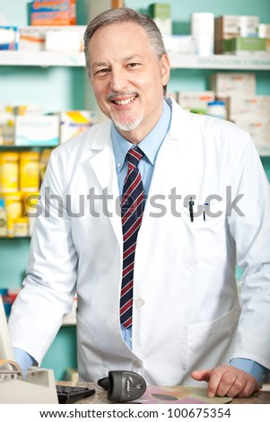 Mature pharmacist in his store smiling - stock photo