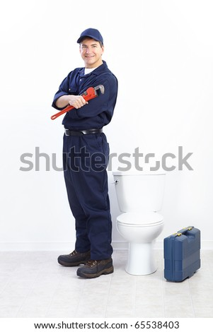 Mature plumber near a flush toilet - stock photo