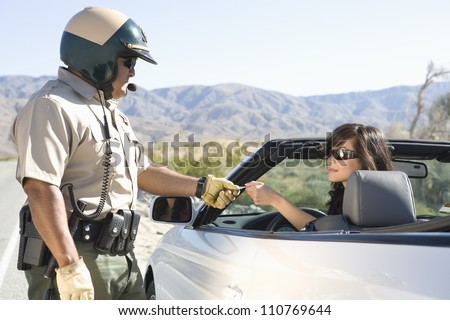 Mature police man checking woman's license - stock photo