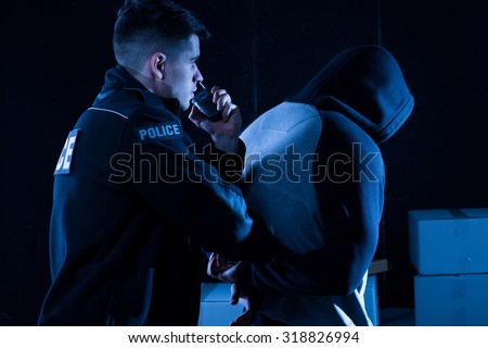 Mature policeman arresting law-breaker at night - stock photo