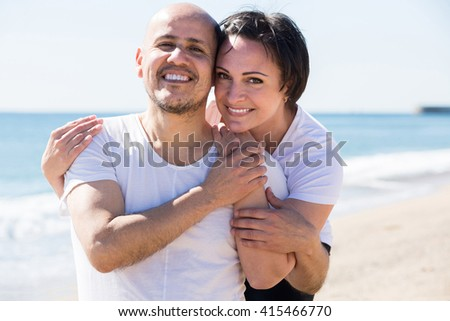 mature positive couple smiling holding each other on the beach