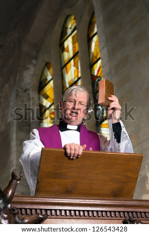 Mature preacher on wooden pulpit during mass - stock photo