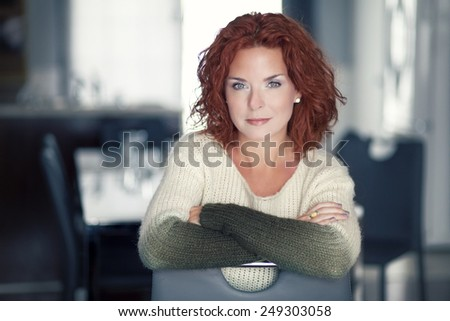 Mature red woman smiling at the camera - stock photo