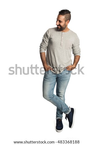Mature relaxed man standing against a white background, wearing a grey shirt and jeans with a big smile on his face.