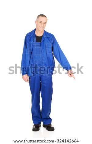 Mature repairman in uniform pointing down. - stock photo