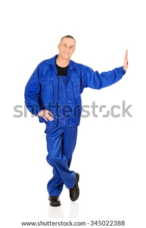 Mature repairman standing against the wall. - stock photo