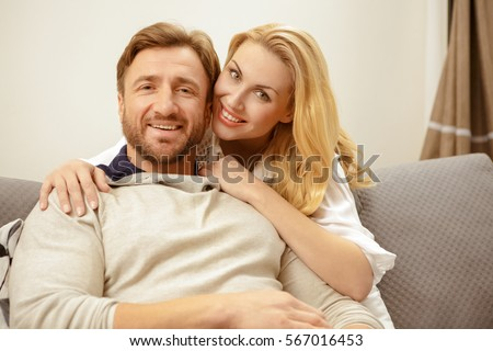 Mature romance. Happy handsome bearded mature man smiling while his beautiful wife embracing him joyful mature couple relaxing at home together home comfort apartment rent love cozy concept copyspace