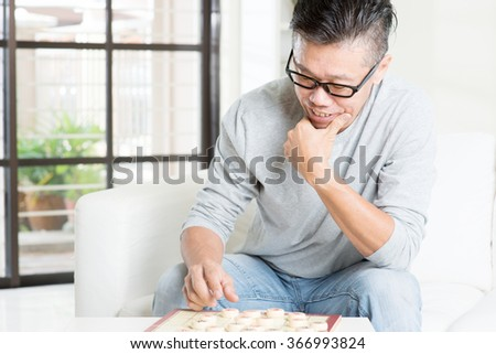 Mature 50s Asian man playing China chess, sitting on couch at home.