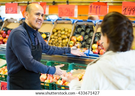 Mature salesman offering female customer good price for fruits in  grocery