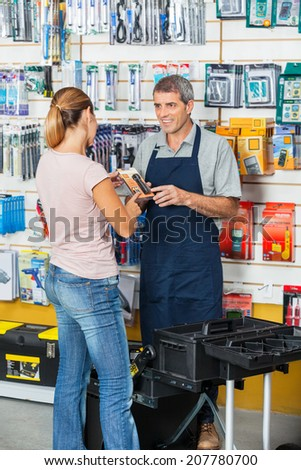 Mature salesman showing flashlight to female customer in hardware store