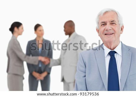 Mature salesman with trading partners behind him against a white background