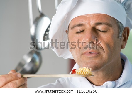 Mature satisfied chef smell the aroma of his food while cooking at restaurant - stock photo