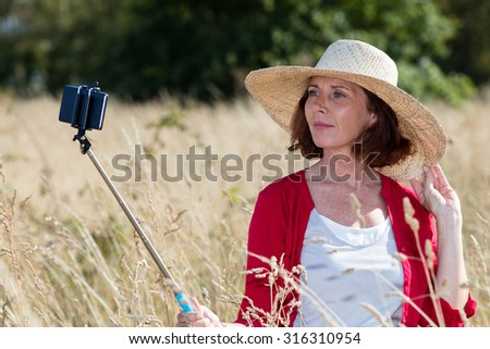 mature selfie concept - beautiful senior woman posing for selfie with a stick in summer dry meadows wearing a chic summer hat,natural daylight