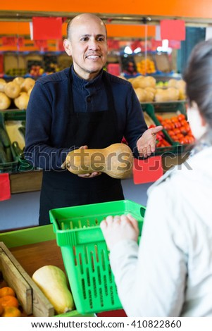 Mature seller offering female fresh squash in local grocery