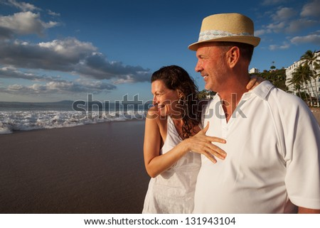 Mature senior adult couple together on tropical beach - stock photo