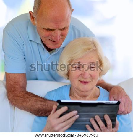 Mature senior couple enjoying modern technology using tablet pc. Elderly people communicating with wireless internet at home. - stock photo