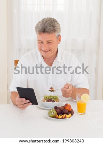 Mature senior man reading with book while sitting at the dining table eating his breakfast of healthy fresh fruit and cereal