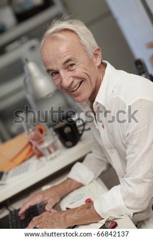 Mature senior typing on his notebook computer - stock photo