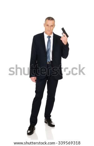 Mature serious mafia agent with handgun. - stock photo