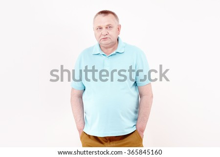 Mature serious man wearing blue shirt and brown trousers standing with hands in pockets and looking aside against white wall - depression concept