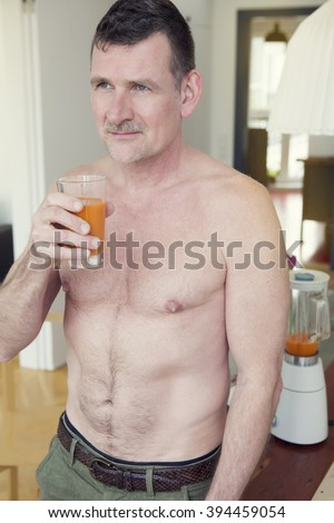 mature shirtless man standing in living room and drinking juice