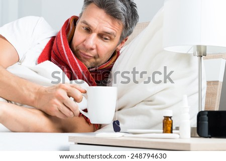 Mature Sick Man Lying On Bed Having Coffee - stock photo