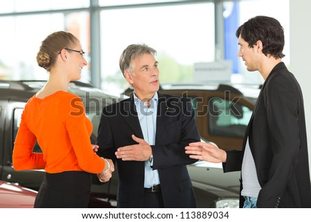 Mature single man with autos, handshaking in light car dealership with a young couple, he obviously is buying a car or is a car dealer - stock photo
