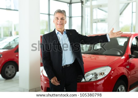 Mature single man with red auto in light car dealership, he is obviously buying a car or is a car dealer - stock photo