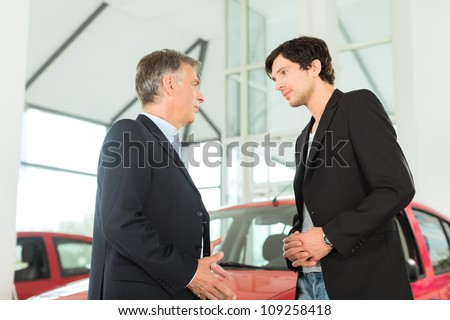 Mature single man with red auto in light car dealership with a male customer, a young man, he is obviously buying a car or is a car dealer - stock photo