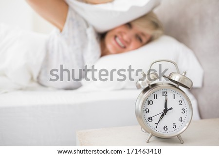 Mature sleepy woman covering ears with pillow in bed with alarm clock in foreground at home