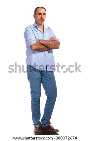 mature smart casual man posing with hands crossed while looking away from the camera in white isolated studio background