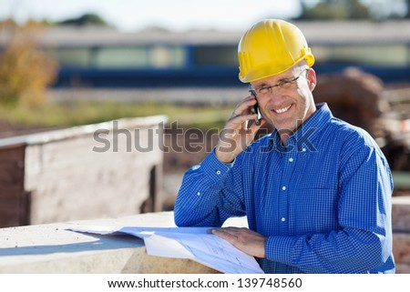 Mature smiling architect while using mobile phone at construction site