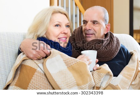 Mature smiling couple in woolen scarf warming up with hot tea - stock photo