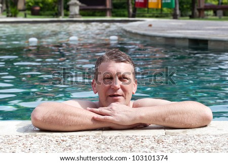mature smiling man in the pool in tropical hotel - stock photo