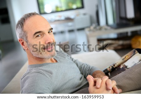 Mature smiling man sitting in couch at home