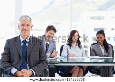 Mature smiling manager sitting in front of his team with his hands crossed - stock photo