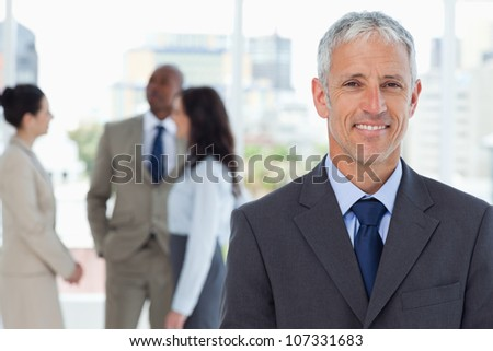 Mature smiling manager standing upright in front of his co-workers
