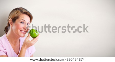 Mature smiling woman with apple. - stock photo