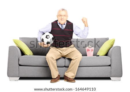 Mature sport fan holding a soccer ball and watching sport isolated on white background